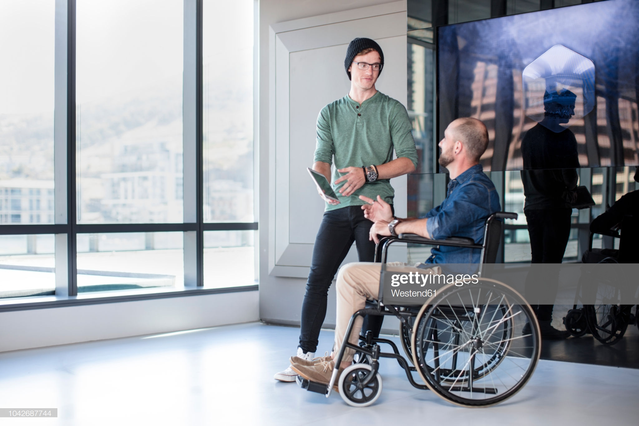 Man talking to handicapped colleague in wheelchair: Stock Photo